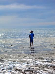 seorang bapak sedang mancing ikan di pinggir pantai